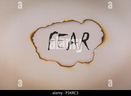 Fear concept, word on burnt paper, toned - Stock Photo