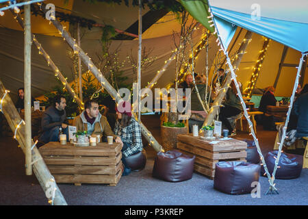London, UK - November 2017. People drinking in a bar and grill tent in Broadgate, where a Nordic-inspired forest called Winter Forest is installed. - Stock Photo
