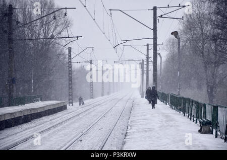 Empty railway station in heavy snowfall with thick fog. Railway rails go away in a white fog of snow. The concept of the railway transport in winter - Stock Photo