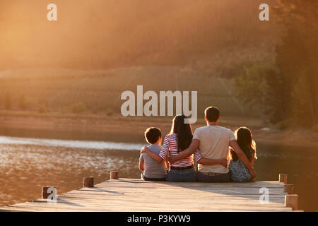 Rear View Of Family Standing On Wooden Jetty By Lake - Stock Photo