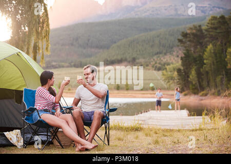 Family Enjoying Camping Vacation By Lake Together - Stock Photo