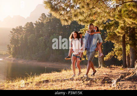 Parents Giving Children Piggyback Rides On Walk By Lake - Stock Photo