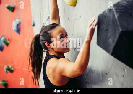 Beautiful young strong woman climbing on red artificial wall top view. - Stock Photo