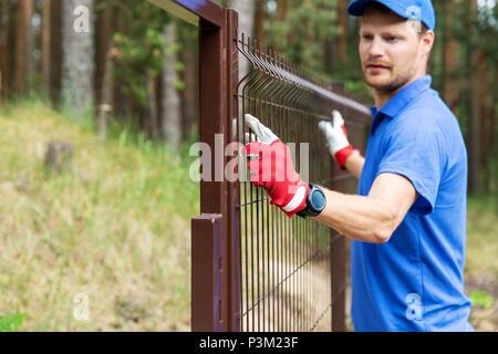 worker installing welded metal mesh fence - Stock Photo