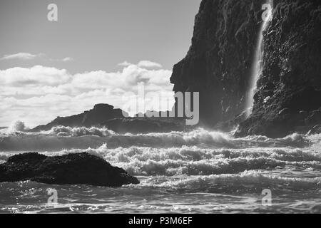 A black and white photograph of waves smashing against Cape Meares, Oregon - Stock Photo