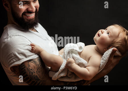 Father holding on hands cute little baby. Family, love and happiness concept - Stock Photo