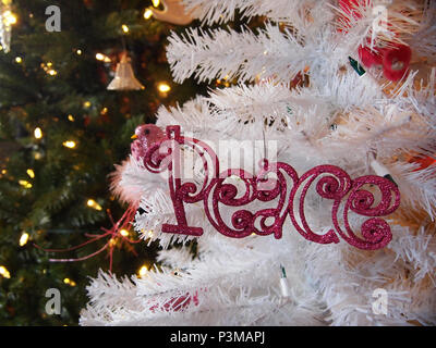 The word PEACE spelled out in pink glittered lettering is an ornament hanging on a white Christmas tree with glowing lighted evergreens in the backgro - Stock Photo