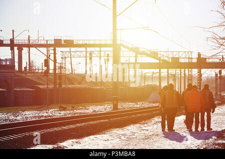 Several railway workers in signaling dirty orange uniforms are on the road next to the railway line. The train crew goes to work in the winter sunny m - Stock Photo