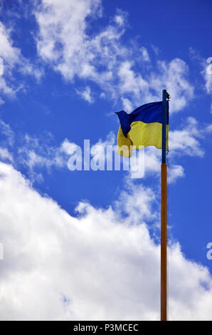 Ukrainian flag against the blue sky with clouds. The official flag of the Ukrainian state includes yellow and blue colors - Stock Photo