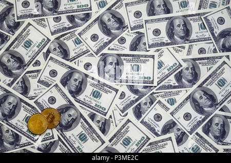 Golden bitcoins lie on a lot of dollar bills. The concept of raising the price of bitcoin relative to the US dollar - Stock Photo