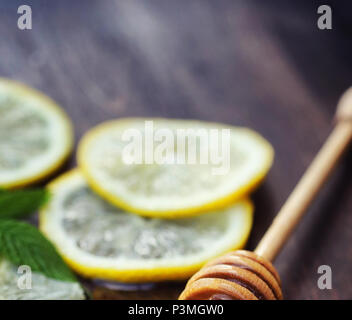 Honey and lemon. Honey stick and slices of sliced lemon on wooden table. Tea in a cup and sweet lime honey in a jar. - Stock Photo