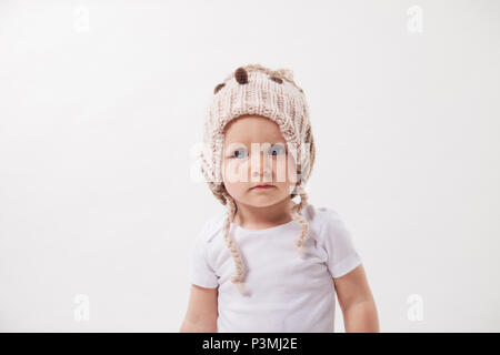 Portrait of a cute baby girl in a huge brown knitted hat. Isolated on white background. - Stock Photo