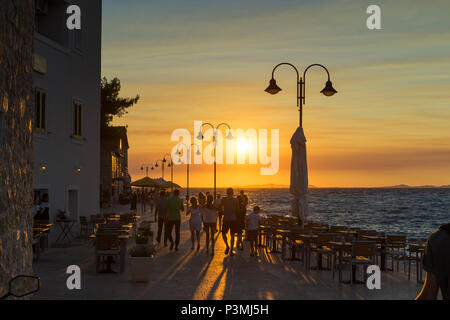 Primosten, Croatia, August 14 2017, People walking on street close Adriatic Sea, Beautiful warm summer evening with colorful sky. - Stock Photo