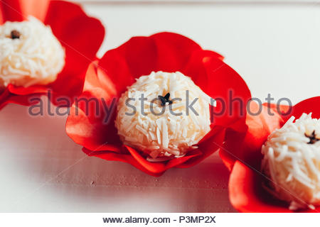 Beijinho is a handmade candy from Brazil. Made with condensed milk and coconut. Children brithday party sweet. - Stock Photo
