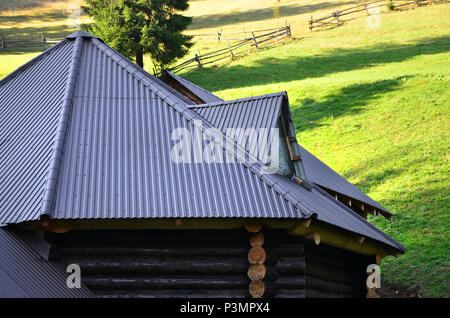 The roof is made of gray embossed metal sheets. Wooden house in the summer field - Stock Photo