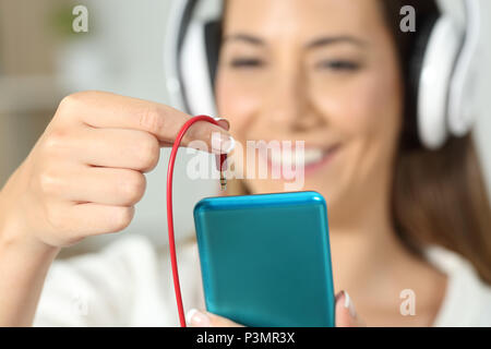 Close up of a happy woman hand plugging jack connector of headphones to the smart phone - Stock Photo