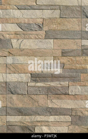 Detail of a wall of a long gray and brown brick. The facade of the building, built of natural stone. Background texture - Stock Photo