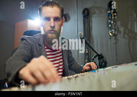 Bearded producer working at console in studio - Stock Photo