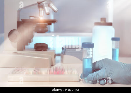Scientific background with microscope room. Shallow DOW, toned image. Focus here is on gloved hand. - Stock Photo