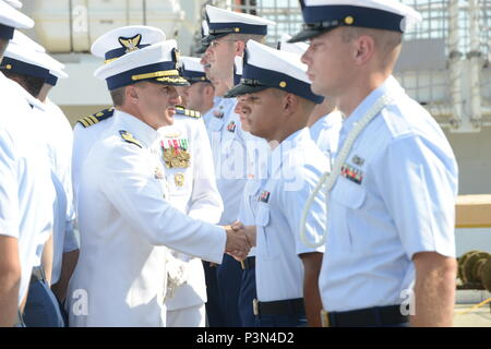 Cmdr. Adam Chamie, center, commanding officer of the Coast Guard Cutter Valiant, conducts a crew inspection as part of the unit's change of command ceremony, July 15, 2016, at Naval Station Mayport, Florida. During the ceremony, Cmdr. Chamie transferred command to Cmdr. Timothy Cronin, whose previous assignment was as deputy chief of enforcement for the Coast Guard 7th District. U.S. Coast Guard photo by Petty Officer 2nd Class Anthony L. Soto - Stock Photo