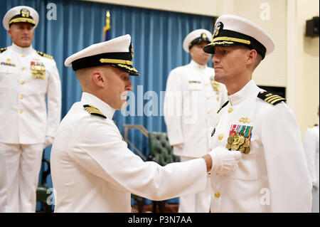160708-N-DH124-055  OKINAWA, Japan (July 8, 2016) - Commander, 30th Naval Construction Regiment, Capt. Jeffrey Killian places the Meritorious Service Medal on Cmdr. Jeffrey Lengkeek during his change of command ceremony on Camp Shields in Okinawa, Japan, Jul. 8.  Cmdr. James Cho, transferring from Naval Facilities Engineering Command (NAVFAC) Southwest relieved Lengkeek, who has orders to Naval Special Warfare Development Group, as commanding officer of Naval Mobile Construction Battalion (NMCB) 4. (U.S. Navy photo by Mass Communication Specialist 1st Class Rosalie Chang/Released) - Stock Photo