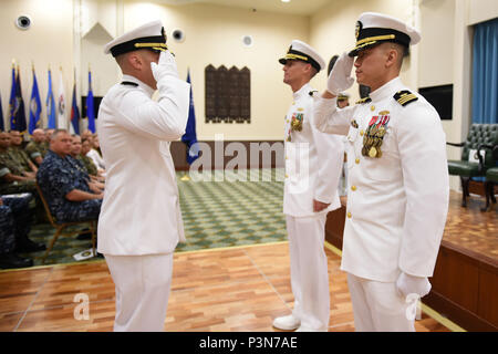 160708-N-DH124-170  OKINAWA, Japan (July 8, 2016) - Cmdr. James Cho salutes Commander, 30th Naval Construction Regiment, Capt. Jeffrey Killian, official taking charge as commanding officer of Naval Mobile Construction Battalion (NMCB) 4 on Camp Shields in Okinawa, Japan, Jul. 8.  Cho transferred from Naval Facilities Engineering Command (NAVFAC) Southwest, serving as the Public Works Officer at Naval Base San Diego.  (U.S. Navy photo by Mass Communication Specialist 1st Class Rosalie Chang/Released) - Stock Photo