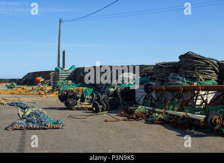 Fishing nets and lobster pots stored on the quayside and against the harbour wall at Kilkeel in County Down Northern Ireland - Stock Photo