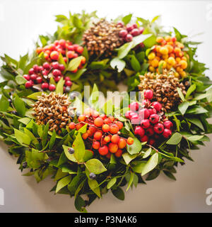 Top view of a festive Christmas wreath with red and orange berries on a white background. Vintage filter. Square format. - Stock Photo