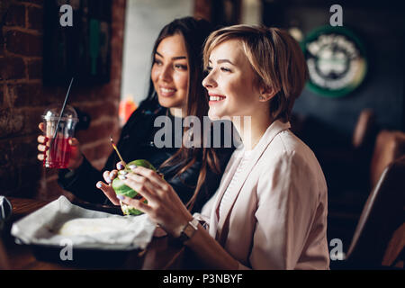 Two girl friends having supper with green sandwich in burger bar. - Stock Photo