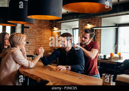 Cheerful gyu and girl having fun arm wrestling each other in pub. - Stock Photo
