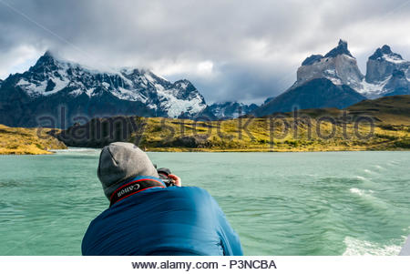 Professional photographer taking photo of Paine Horns with Canon Eos 6D camera, Lake Pehoe, Torres del Paine National Park, Patagonia, Chile - Stock Photo