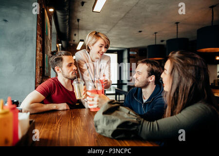 Happy friends drinking beverages having fun while spending time together in cafe - Stock Photo
