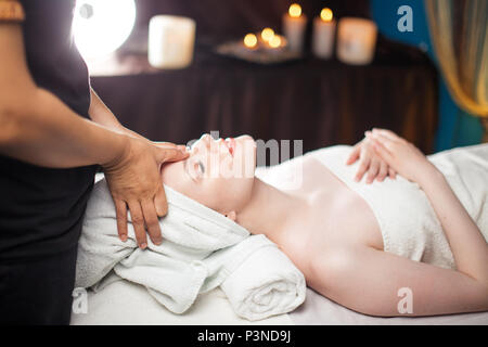 Healthful Leisure Time. Satisfied woman having face massage in spa complex. - Stock Photo