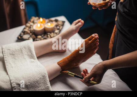 Masseuse applying chocolate substance on female legs during massage in spa salon - Stock Photo