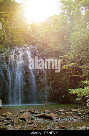 Beautiful waterfall cascading over rock into deep aqua colored water surrounded by dense jungle rainforest - Stock Photo