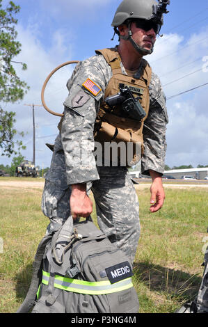 New York Army National Guard Sgt. Hendry Rodman, a senior medic assigned to Co. B., 1st Battalion, 69th Infantry, New York City grabs his gear in preparation for movement during training at the Joint Readiness Training Center, Ft. Polk, La., Friday, July 15. The medics joined more than 5,000 Soldiers from other state Army National Guard units, active Army and Army Reserve troops as part of the 27th Infantry Brigade Combat Team task force.  The Soldiers will hone their skills and practice integrating combat operations ranging from infantry troops engaging in close combat with the enemy to artil - Stock Photo