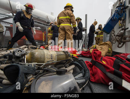 160716-N-DJ750-035  SAN DIEGO (July 16, 2016) Sailors aboard Avenger-class Mine Countermeasures Ship USS Champion (MCM 4) don fire-fighting gear during a damage control training exercise in support of the Southern California portion of Rim of the Pacific 2016. Twenty-six nations, more than 40 ships and submarines, more than 200 aircraft and 25,000 personnel are participating in RIMPAC from June 30 to Aug. 4, in and around the Hawaiian Islands and Southern California. The world's largest international maritime exercise, RIMPAC provides a unique training opportunity that helps participants foste - Stock Photo