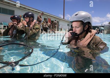 Australian Army soldier Lance Corporal Natasha Sant from 2nd Battalion, Royal Australian Regiment, practises using an emergency breathing device during shallow-water egress training for Exercise Rim of the Pacific (RIMPAC) 2016. (Australian Defence Force photo by Cpl David Said) - Stock Photo