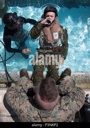 An Australian Army soldier from 2nd Battalion, Royal Australian Regiment, practises using an emergency breathing device during shallow-water egress training with United States Marine Corps amphibious reconnaissance marines for Exercise Rim of the Pacific (RIMPAC) 2016. (Australian Defence Force photo by Cpl David Said) - Stock Photo