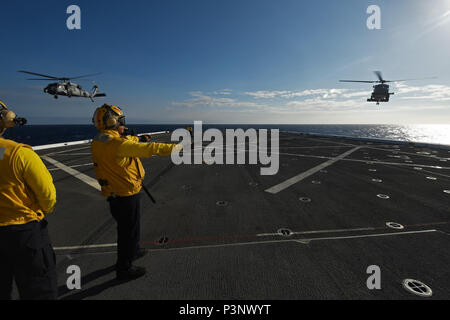 160716-N-RC734-249  PACIFIC OCEAN (July 16, 2016) - An MH-60S Sea Hawk, assigned to the 'Red Lions' of Helicopter Sea Combat Squadron (HSC) 15, lifts off from the flight deck of amphibious transport dock ship USS San Diego (LPD 22) while an MH-60R Sea Hawk, assigned to the 'Magicians' of Helicopter Maritime Strike Squadron (HSM) 35, makes it's approach during Rim of the Pacific 2016. Twenty-six nations, more than 40 ships and submarines, more than 200 aircraft and 25,000 personnel are participating in RIMPAC from June 30 to Aug. 4, in and around the Hawaiian Islands and Southern California. Th - Stock Photo