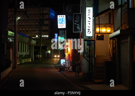 Night shot of empty street in Aomori, Japan, with car headlights at the end of the road and Japanese neon banners as the only light source. - Stock Photo