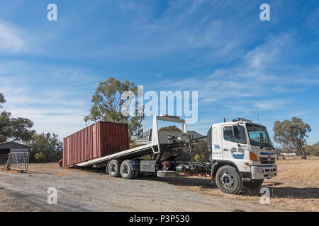 An old shipping container being loaded onto a Hino 500 Series GH tipper truck. - Stock Photo