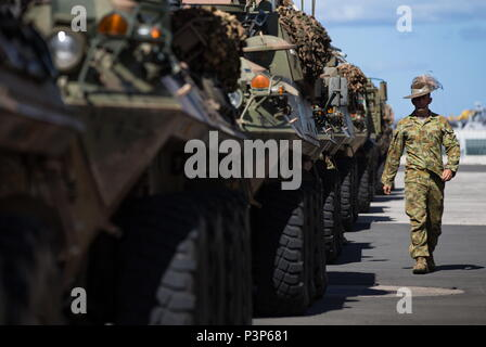 Australian Army soldier Lance Corporal Joel Roveda from the 2nd Cavalry Regiment walks past a line of Australian Army Light Armoured Vehicles on the wharf at Joint Base Pearl Harbor-Hickam ready to be loaded onto HMAS Canberra during Exercise Rim of the Pacific 2016. (Australian Defence Force photo by Cpl David Said) - Stock Photo