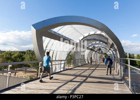 Madrid, Spain: Pedestrians cross the Arganzuela Footbridge over the Manzanares River. The modern pedestrian way connects the Arganzuela and Carabanche - Stock Photo