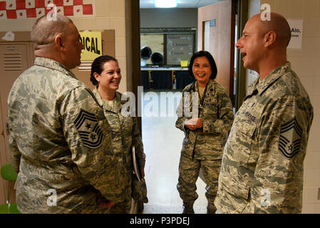 U.S. Air Force Command Chief Master Sgt. Jose Gonzalez from 177th Fighter Wing, left, Command Chief Master Sgt. Janeen Fillari, New Jersey State Command Chief, center left, and Chief Master Sgt. James McCloskey, 177th Fighter Wing, right, speak with Lt. Col. Mauricia Alo, 108th Medical Group, during the Healthy Cortland event at Homer Intermediate School in Homer, N.Y., July 20, 2016. Service members provided no cost medical, dental, optometry, and veterinary care to local citizens. (U.S. Air National Guard photo by Senior Airman Julia Santiago) - Stock Photo