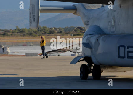 160711-N-IL474-129 SOUDA BAY, Greece (July 11, 2016) Aviation Boatswain's Mate (Handling) Airman Apprentice Alaina Growney, assigned to U.S. Naval Support Activity Souda Bay Air Operations Department Transient Line Division, directs an MV-22 Osprey following its arrival.  NSA Souda Bay enables the forward operations and responsiveness of U.S. and allied forces in support of Navy Region, Europe, Africa and Southwest Asia's mission to provide services to the Fleet, Fighter, and Family. (U.S. Navy photo by Heather Judkins/Released) - Stock Photo