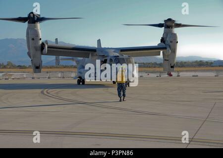 160711-N-IL474-154 SOUDA BAY, Greece (July 11, 2016) Aviation Boatswain's Mate (Equipment) 3rd Class Adrian Brown, assigned to U.S. Naval Support Activity Souda Bay Air Operations Department Transient Line Division, directs an MV-22 Osprey following its arrival.  NSA Souda Bay enables the forward operations and responsiveness of U.S. and allied forces in support of Navy Region, Europe, Africa and Southwest Asia's mission to provide services to the Fleet, Fighter, and Family. (U.S. Navy photo by Heather Judkins/Released) - Stock Photo