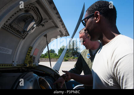 """Brig. Gen. Jon T. Thomas, 86th Airlift Wing commander, inspects the engine of a C-130J Super Hercules alongside Staff Sgt. Dominiq Saxon, 86th Aircraft Maintenance Squadron aircraft hydraulics systems journeyman, during his """"fini flight"""" July 20, 2016, at Ramstein Air Base, Germany. Thomas helped Saxon as he repaired the hydraulics system of the plane after it malfunctioned prior to takeoff. (U.S. Air Force photo/Airman 1st Class Lane T. Plummer) - Stock Photo"""