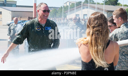 """Brig. Gen. Jon T. Thomas, 86th Airlift Wing commander, approaches his family as he gets hosed down with water during his """"fini flight"""" July 20, 2016, at Ramstein Air Base, Germany. Fini flights have been a tradition for pilots that are changing bases since World War II. The pilots fly their assigned aircraft one last time, and are greeted by Airmen, family and friends after landing. (U.S. Air force photo/Airman 1st Class Lane T. Plummer) - Stock Photo"""