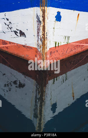 Water reflection of a front of a small empty fisherman boat moored in port - Stock Photo